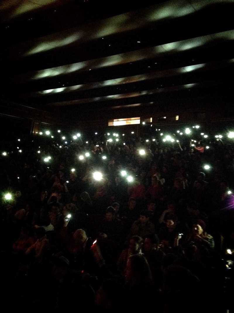Audience members wave their cell phones to the beat during the last song.